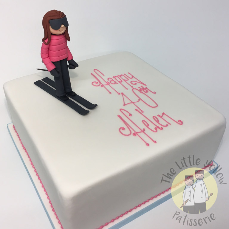 The Little Yellow Patisserie Celebration Cakes (White square cake with a fondant woman skiing on top)