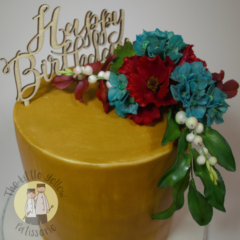 The Little Yellow Patisserie Celebration Cakes (gold cake with fondant flowers and a happy birthday sign on top)