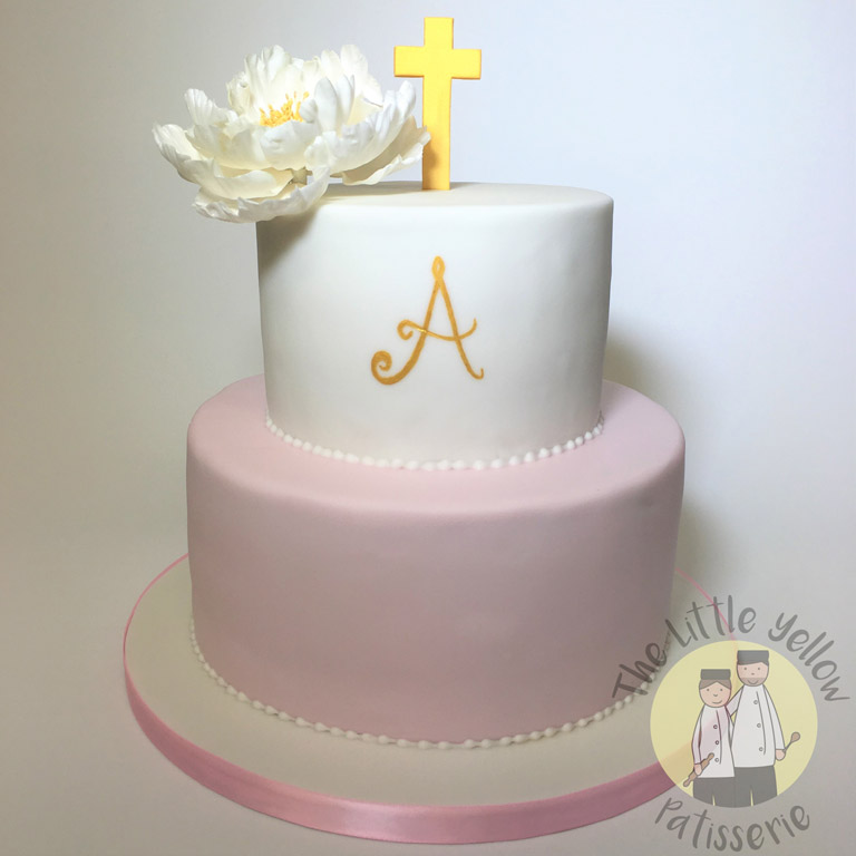 The Little Yellow Patisserie Celebration Cakes (white and pink tiered cake with a gold cross on top)