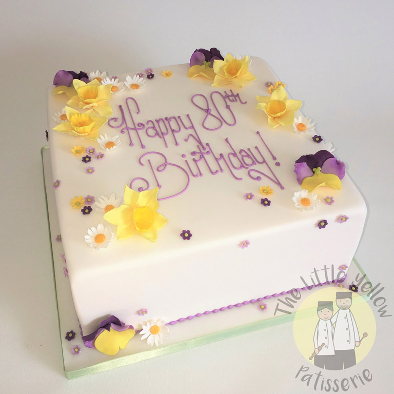 The Little Yellow Patisserie Celebration Cakes (White square cake with fondant purple and yellow flowers)