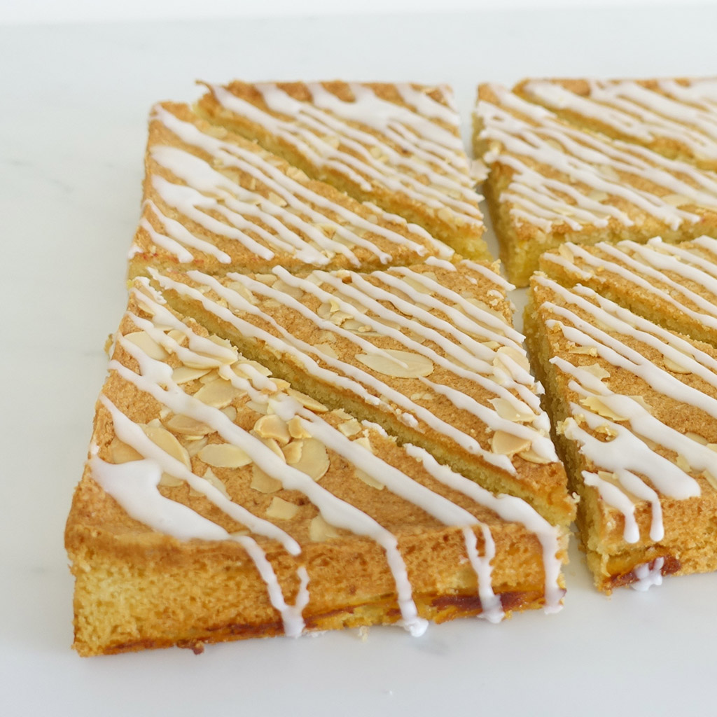 The Little Yellow Patisserie Lemon Bakewell Traybake (triangles of bakewell with white drizzled icing and almond flakes)
