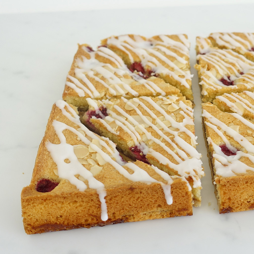 The Little Yellow Patisserie Raspberry Bakewell (triangles of bakewell sponge with raspberry chunks, drizzled with white icing and almond flakes)